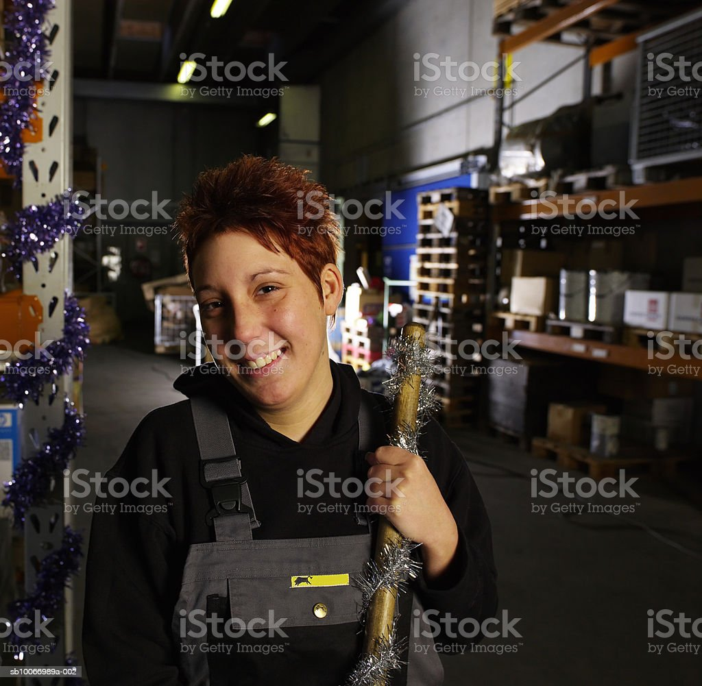 Young woman holding broom in warehouse, portrait royalty-free stock photo