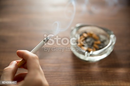 Young woman holding burning cigarette in hand with ashtray