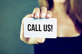 istock Young woman holding call us card 1039540532