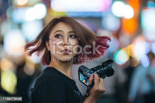 A young woman is holding a digital  camera at night.