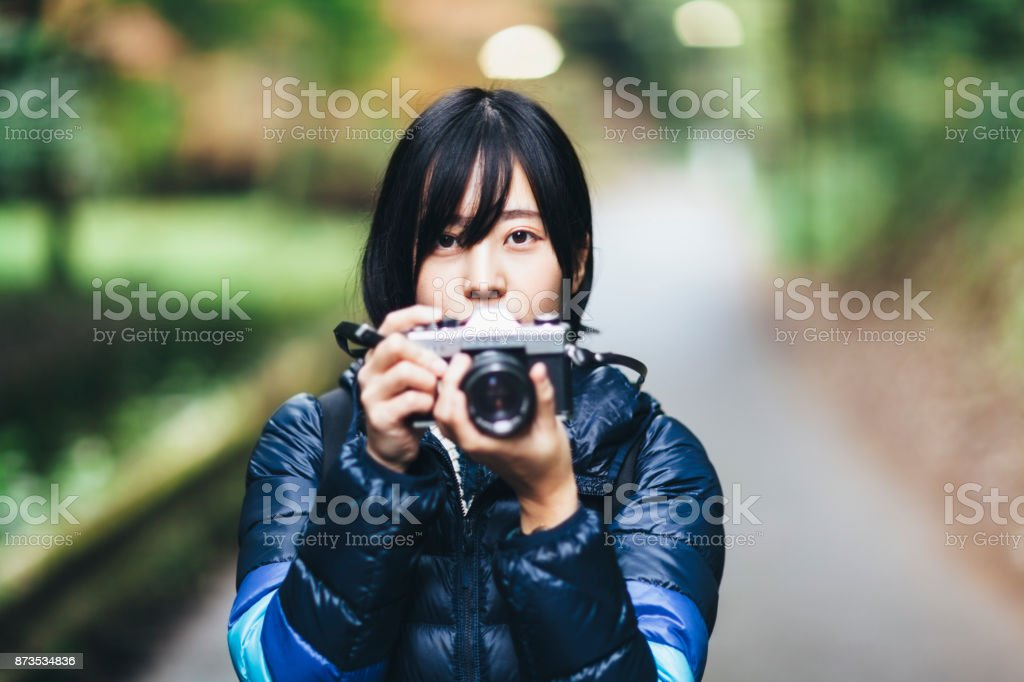 Young Woman Holding Camera In Nature stock photo