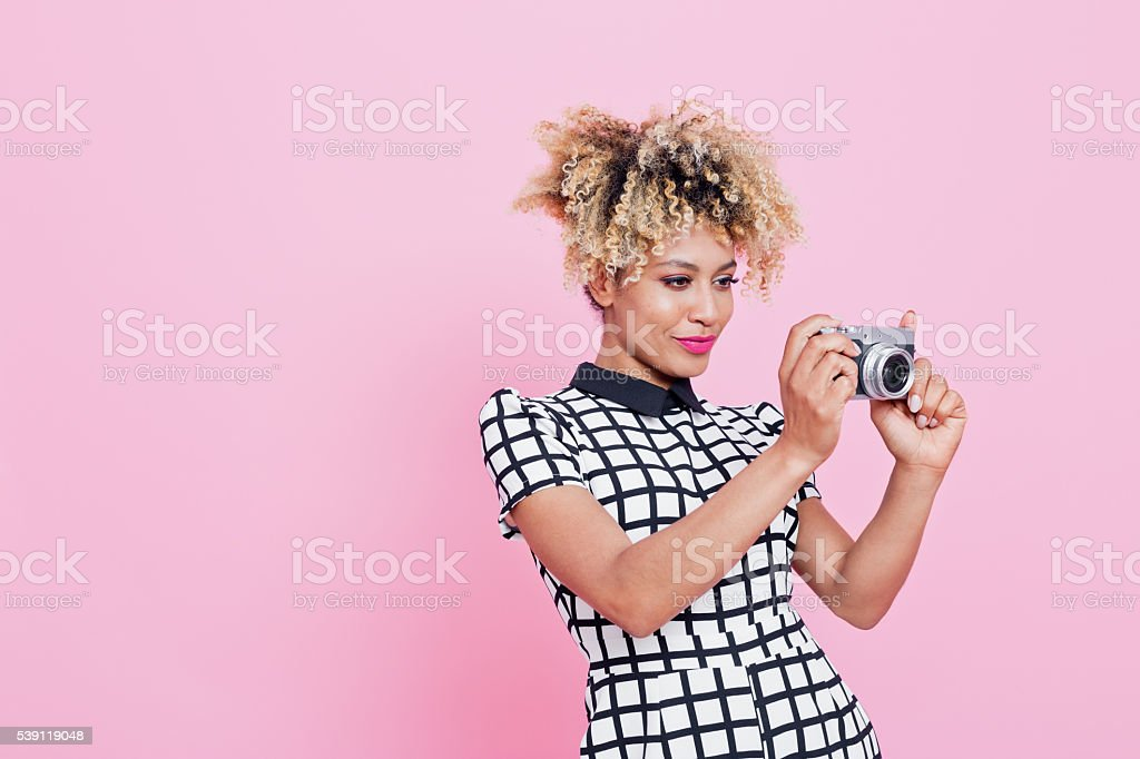 Young woman holding camera Portrait of beautiful afro american young woman. Wearing grid check playsuit, standing against pink background and holding camera. Studio shot, one person. 25-29 Years Stock Photo