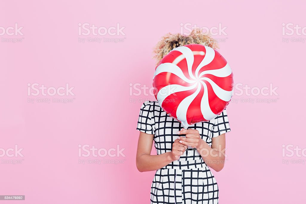 Young woman holding candy shaped balloon Portrait of unrecognisable young woman, wearing grid check playsuit, standing against pink background and hide her face behind Candy Balloon. 2016 Stock Photo