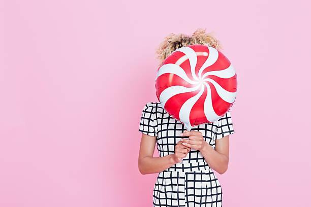 junge frau hält süßigkeiten geformte ballon - frisuren 2016 frauen stock-fotos und bilder