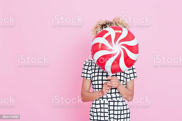 Young Woman Holding Candy Shaped Balloon Stock Photo - Download Image Now