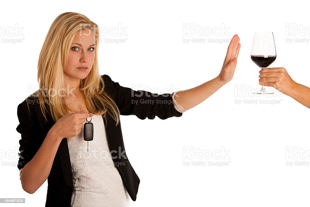Young woman holding car keys and refusing a glass of wine stock photo