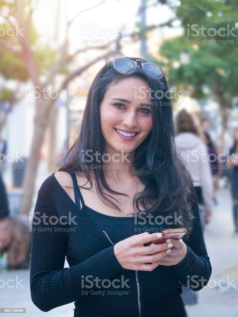Young woman holding cell phone, Third Street Promenade, Santa Monica stock photo