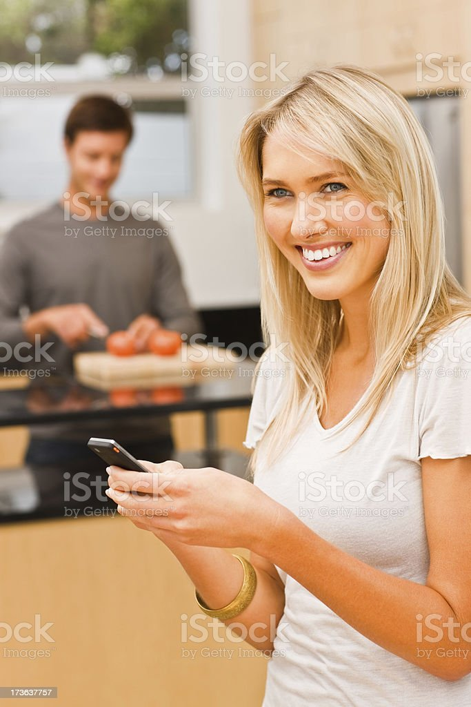 Young woman holding cellphone while man cutting vegetable in background royalty-free stock photo