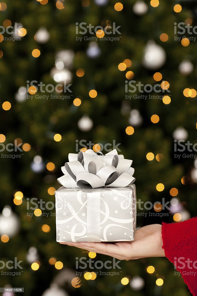 Young Woman Holding Christmas Gift with Lights and Tree royalty-free stock photo