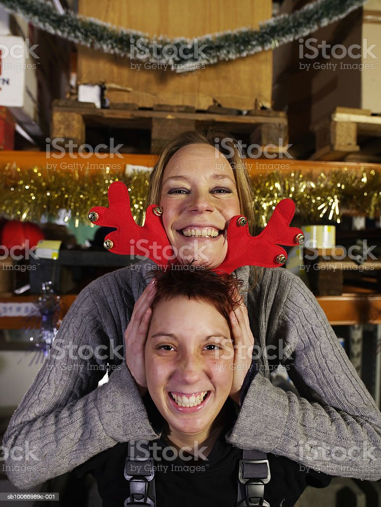 Young woman holding christmas reindeer antlers on other women's  head, portrait royalty-free stock photo