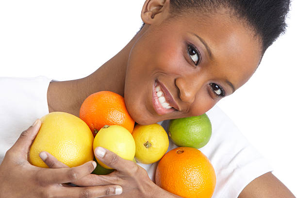 Junge Frau hält Zitrusfrucht In Studio – Foto