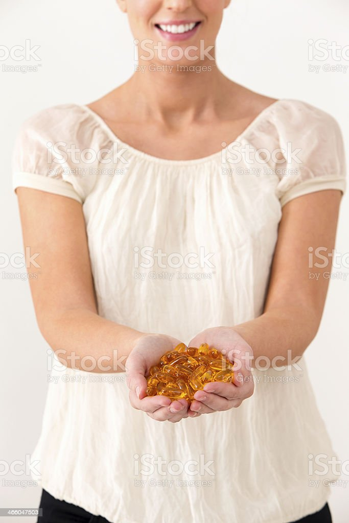 Young Woman Holding Cod Liver Oil Pills royalty-free stock photo