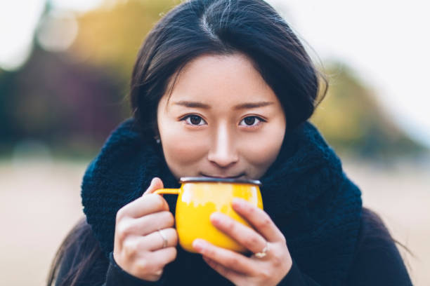 Young Woman Holding Coffee Cup And Looking At Camera stock photo