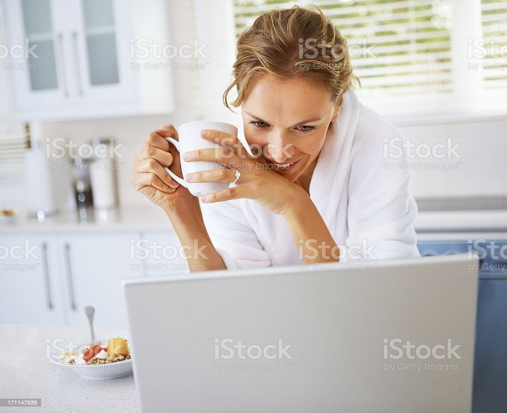 Young woman holding coffee cup and looking at laptop royalty-free stock photo