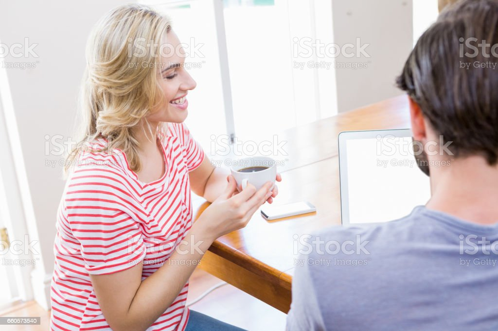 Young woman holding coffee mug while man using laptop royalty-free stock photo