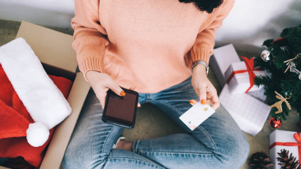 Young woman holding credit card and doing shopping online. stock photo