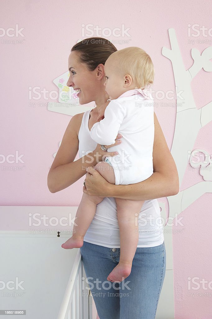 Young woman holding cute baby and looking away royalty-free stock photo