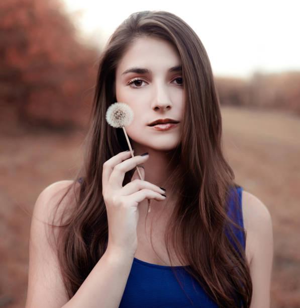 Mujer joven sosteniendo diente de León - foto de stock