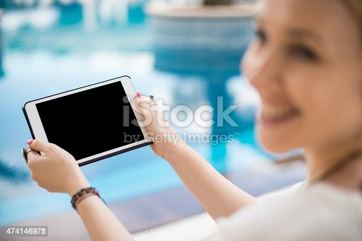 863476202istockphoto Young woman holding digital tablet 474146978