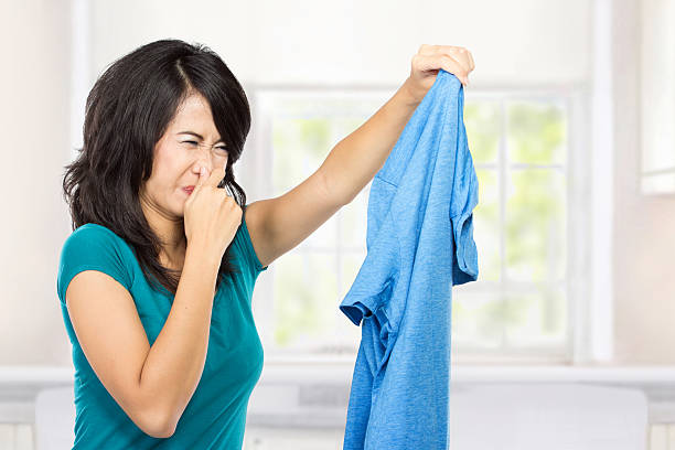 young woman holding dirty clothes stock photo