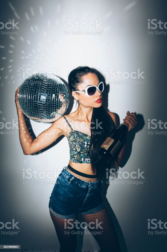 Direct flash portrait of cheerful party girl holding disco ball and...