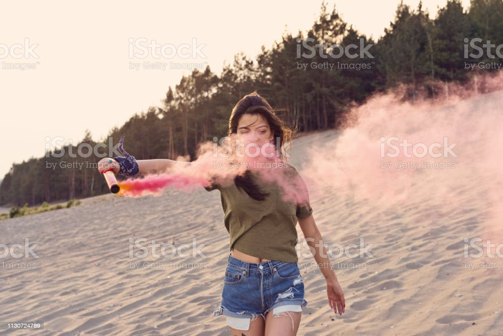 Young woman holding distress flare at desert Beautiful woman holding pink distress flare at desert. Young female is enjoying during vacation. Hipster is hiking and having fun on sand. 25-29 Years Stock Photo