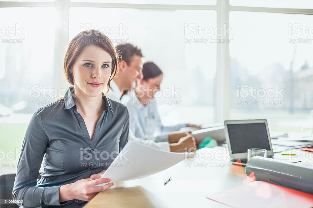 Young woman holding documents with colleagues in background at office – Foto