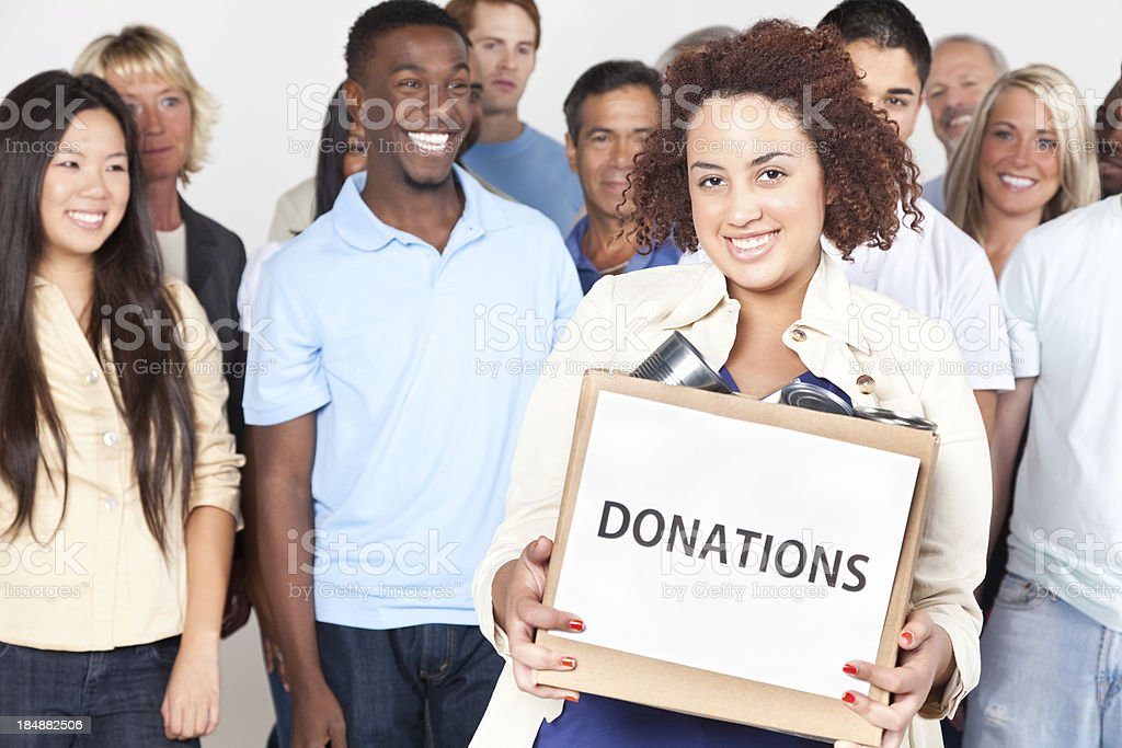 Young woman holding donation box in front of group royalty-free stock photo
