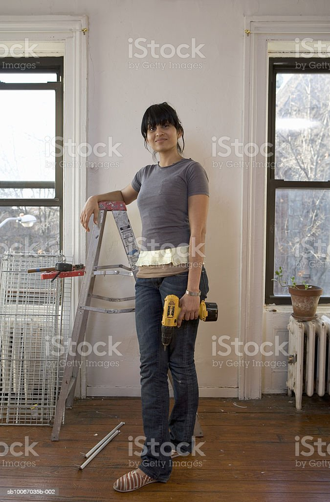Young woman holding drill, smiling, portrait foto de stock libre de derechos