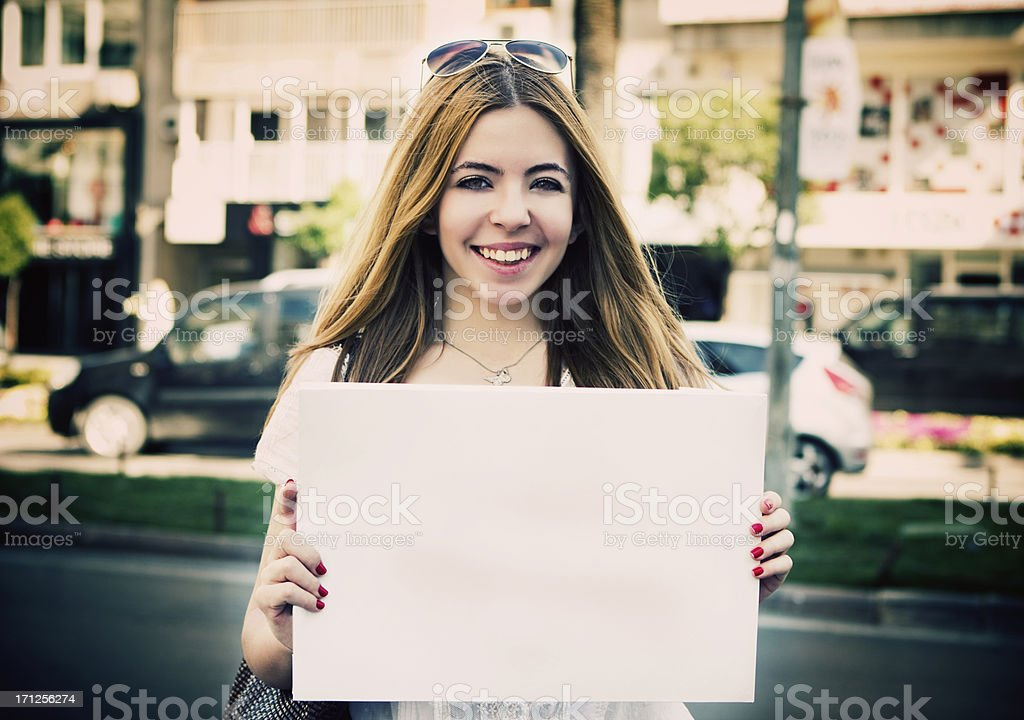Young woman holding empty white placard stock photo