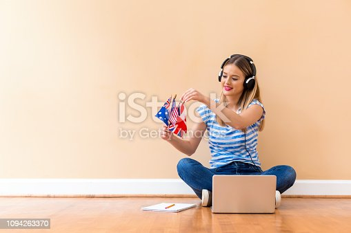 Young woman with English speaking country flags using a laptop computer against a big interior wall