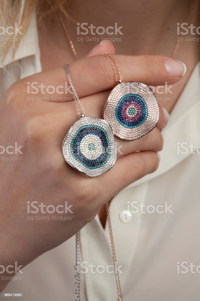 Young Woman Holding Evil Eye Silver Necklaces royalty-free stock photo
