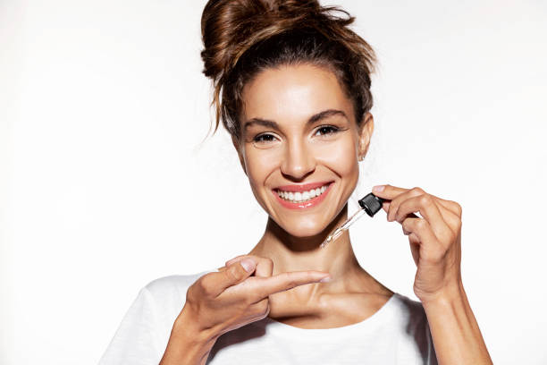 Young woman holding  face oil. stock photo