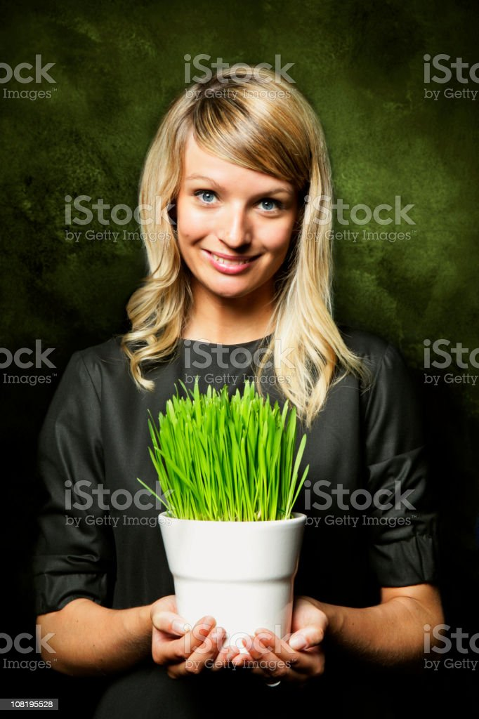 Young Woman Holding Flower Pot of Green Grass royalty-free stock photo