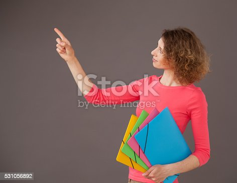 istock Young woman holding folders and indicating something up 531056892