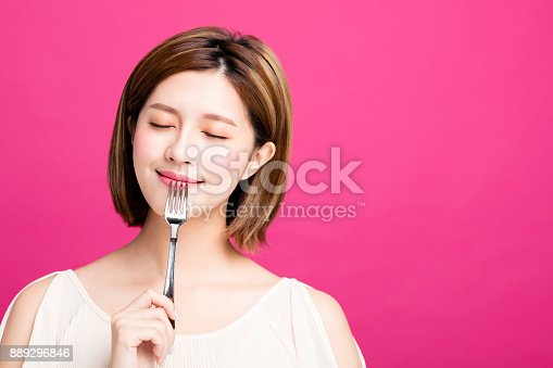 young woman holding fork and enjoy tasty food