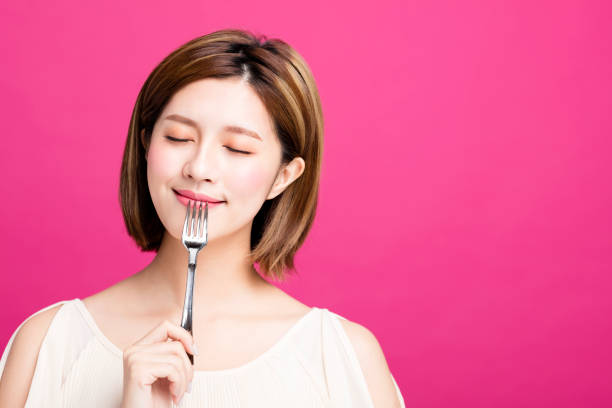 young woman holding fork and enjoy tasty food stock photo