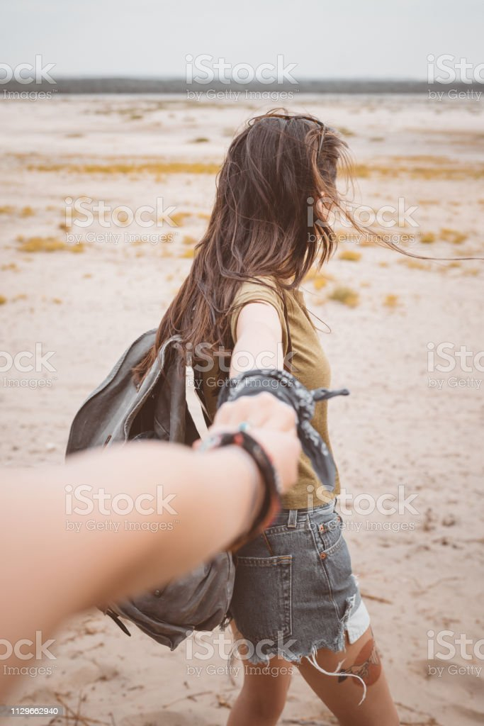 Young woman holding friend's hand at desert Young woman holding friend's hand at desert. Females are spending leisure time on sand. They are enjoying vacation. 20-24 Years Stock Photo