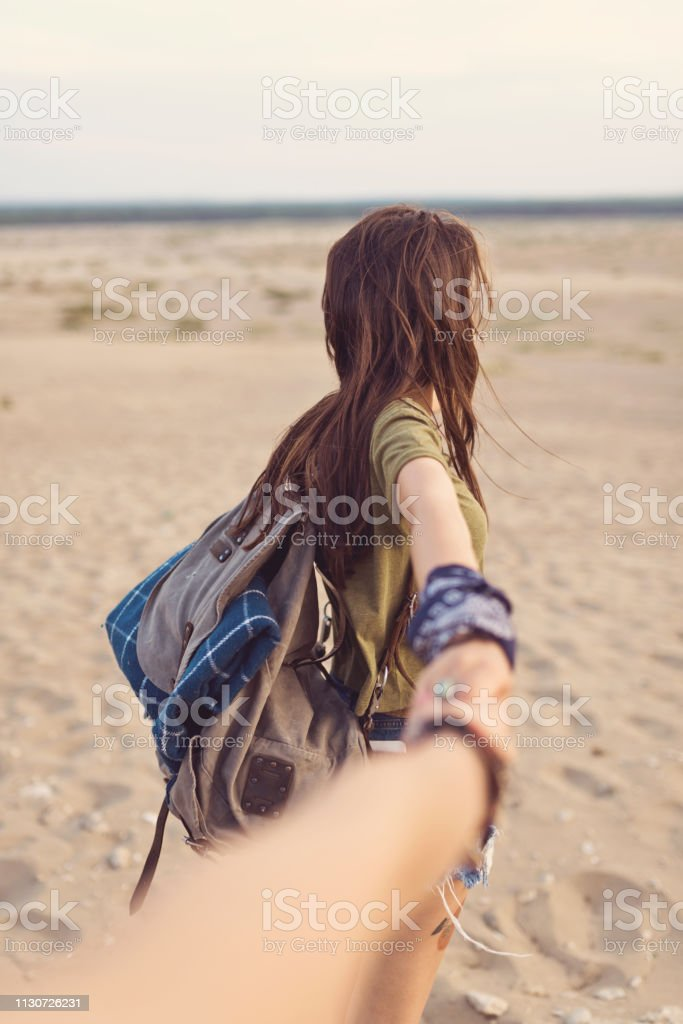 Young woman holding friend's hand in desert Young brunette woman holding friend's hand. Female backpacker is hiking in desert. She is spending leisure time with friend. 20-24 Years Stock Photo