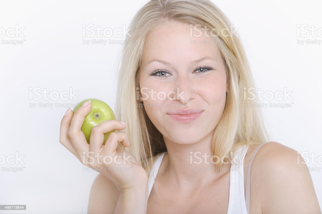 Young woman holding fruit against white background,portrait,smil stock photo