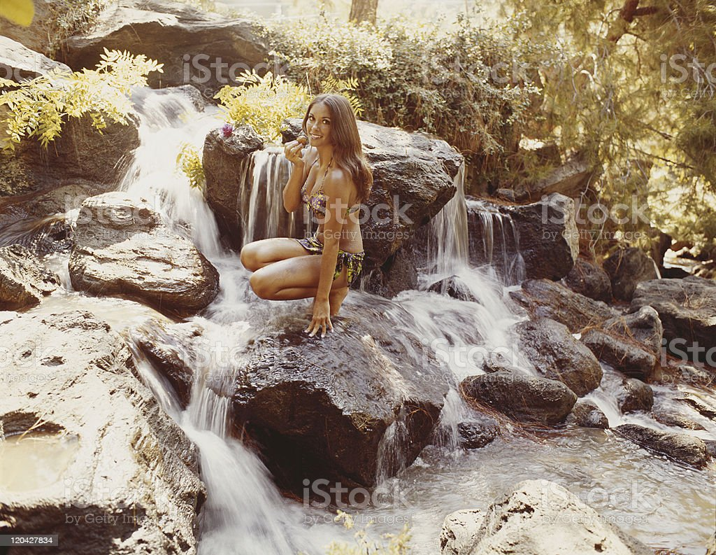 Young woman holding fruit on waterfall, smiling, portrait stock photo