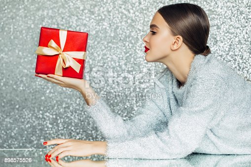 istock Young woman holding gift box in her hands 898575526