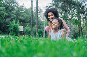 istock Young woman holding girl doing yoga in the park 1023023434