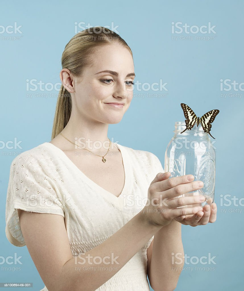 Young woman holding glass jar with butterfly, studio shot 免版稅 stock photo