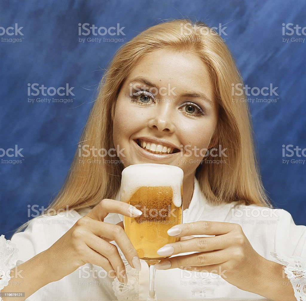 Young woman holding glass of beer, portrait, close-up stock photo