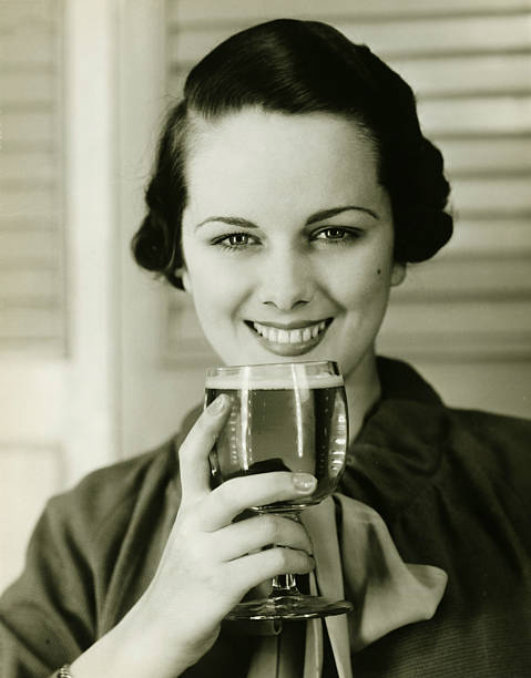 Young woman holding glass of beer, (B&W), portrait stock photo