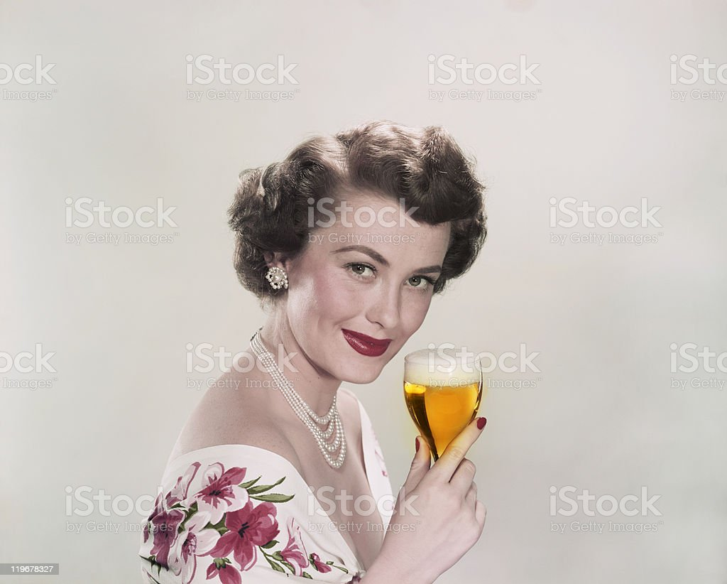 Young woman holding glass of beer, smiling, portrait​​​ foto