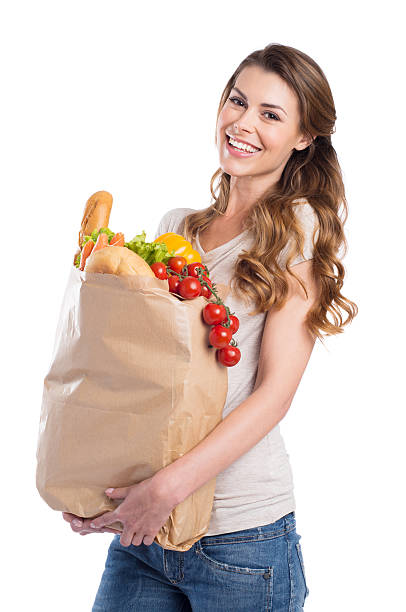 Young Woman Holding Grocery Bag Portrait Of Happy Young Woman Holding Grocery Bag Over White Background grocer stock pictures, royalty-free photos & images
