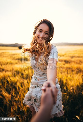 Beautiful country woman in vintage style holding hands with boyfriend in a wheatfield at sunset