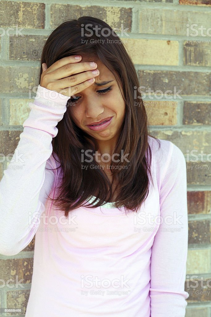 Young woman holding head and looking sad and distressed stock photo